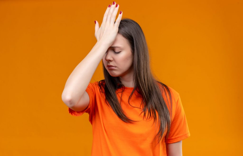 young-beautiful-girl-wearing-orange-t-shirt-standing-with-hand-head-mistake-looking-unhappy-with-sad